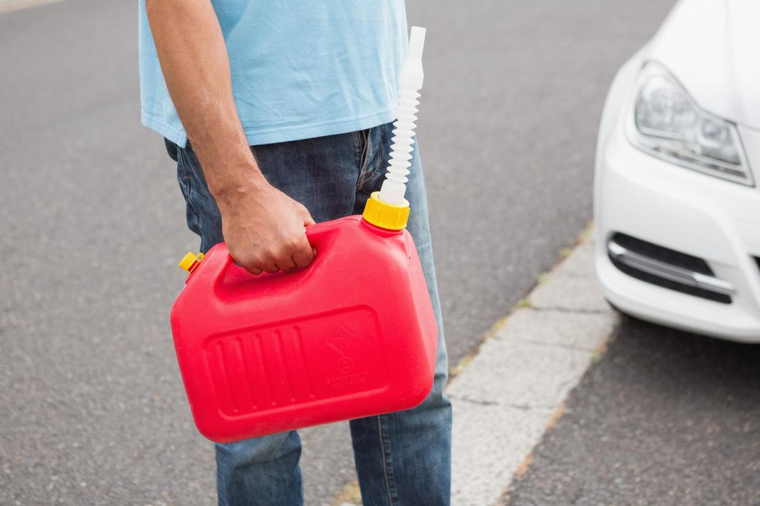 man holding a gas container with a tube